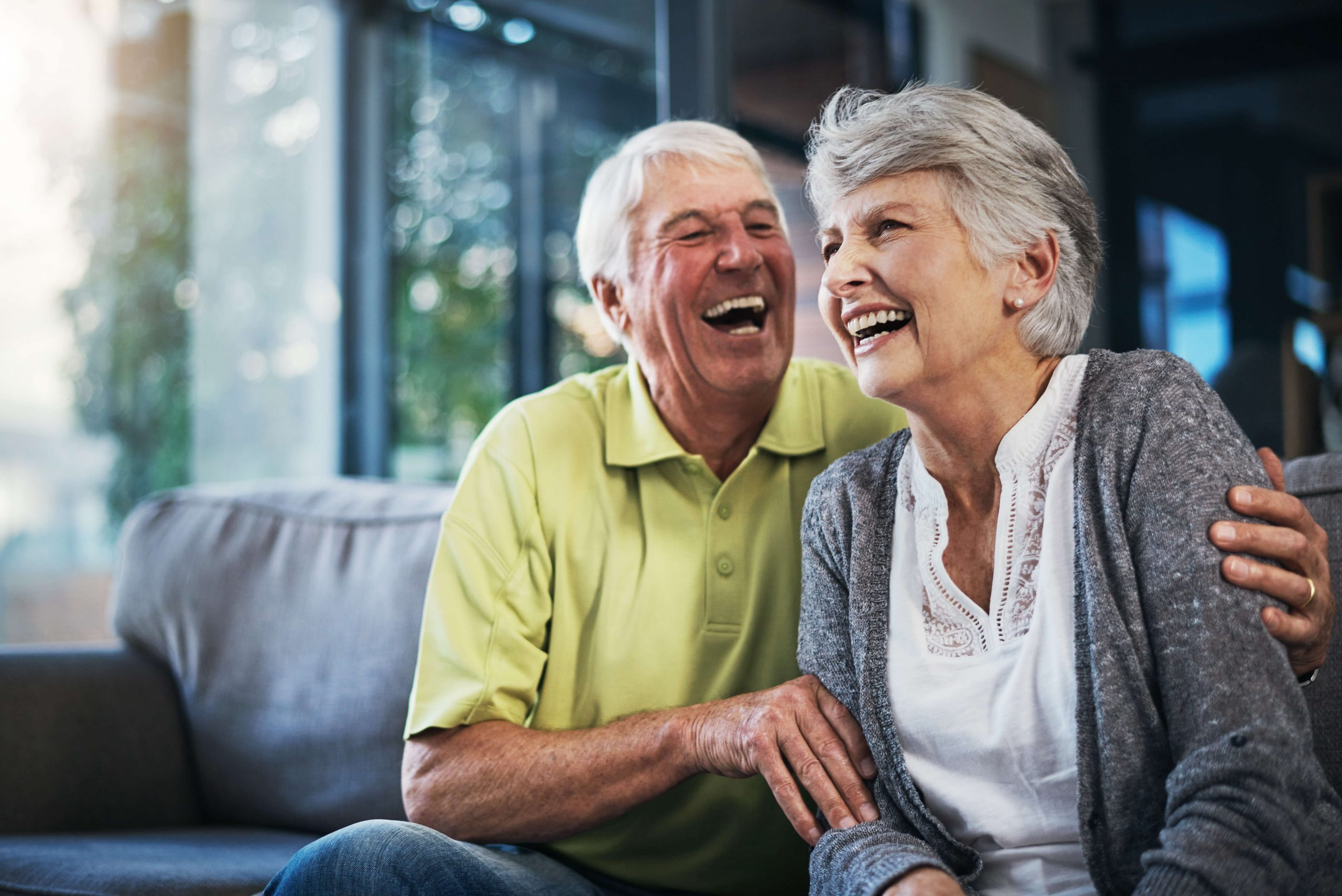 Older couple sitting on a couch and laughting